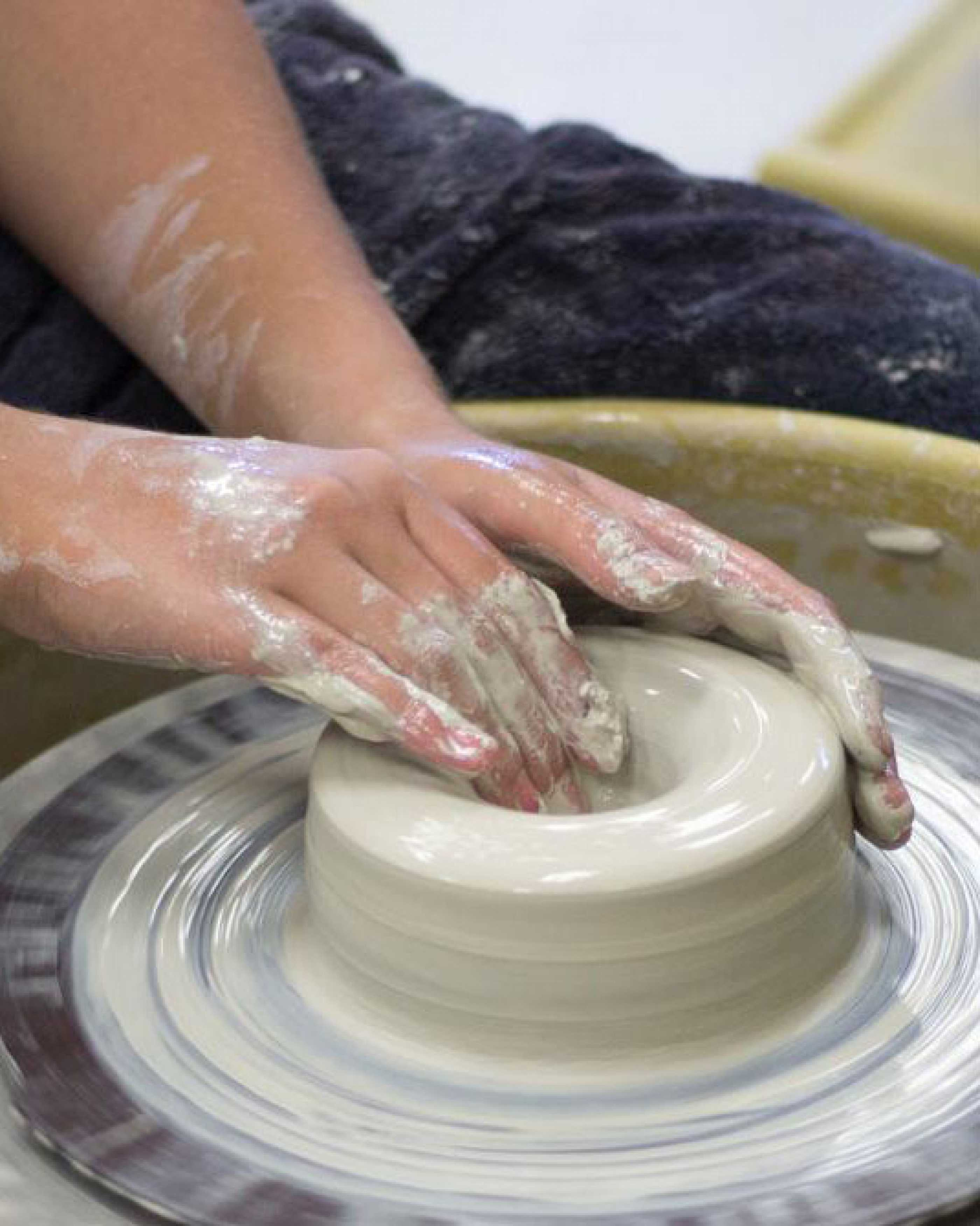 Student working with clay wheel