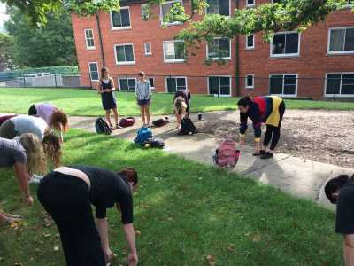 """Intro Art Ed. students listening and participating in outdoor yoga during their """"Teach Anything"""" projects."""